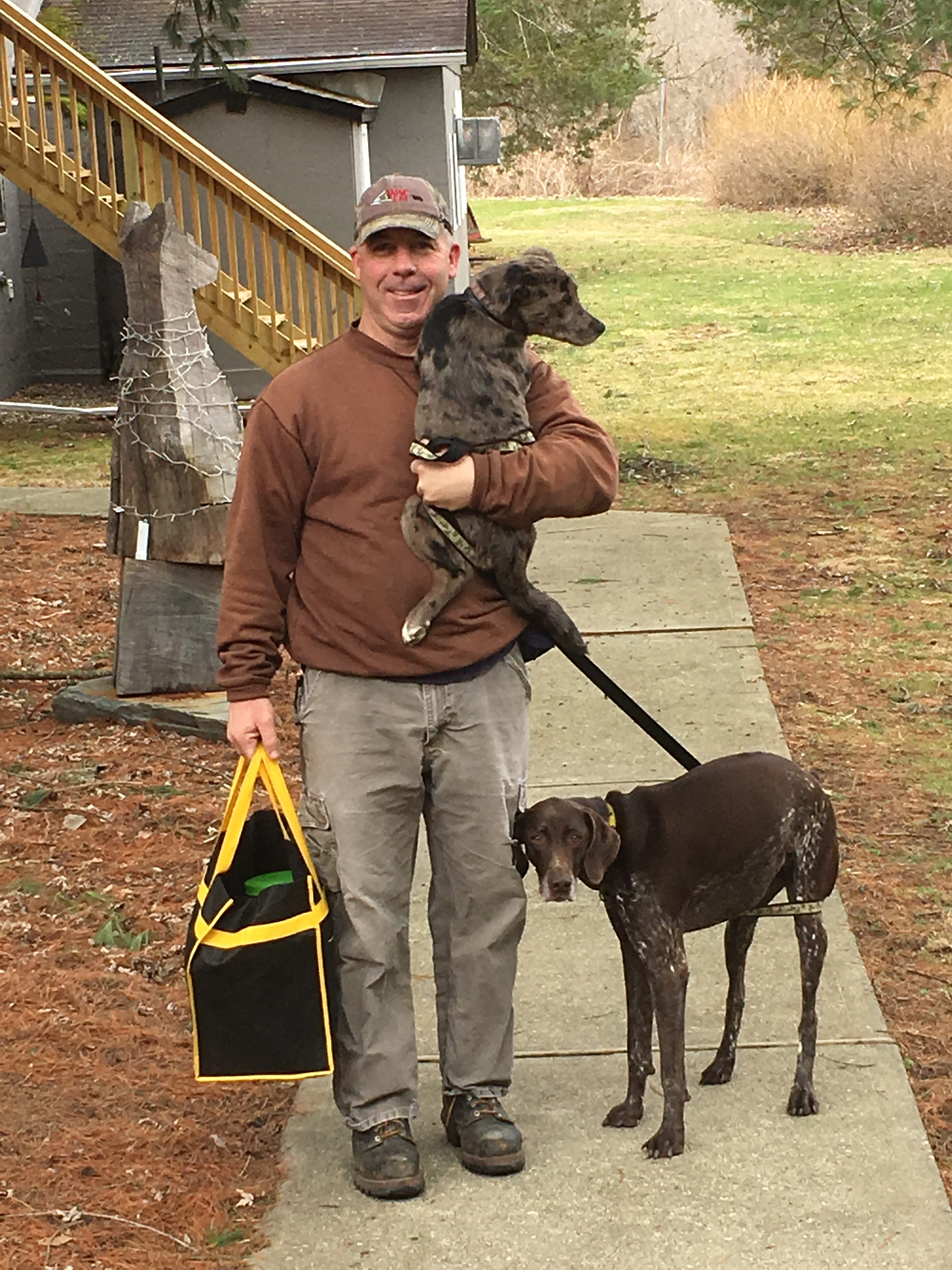photo of dog owner with his two dogs, one in his arms