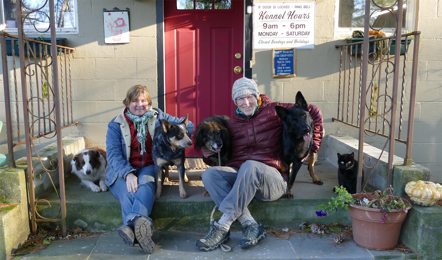 photo of Anne Reagan and Liz Quinn and their dogs and cat in front of Albanhaus Kennel door